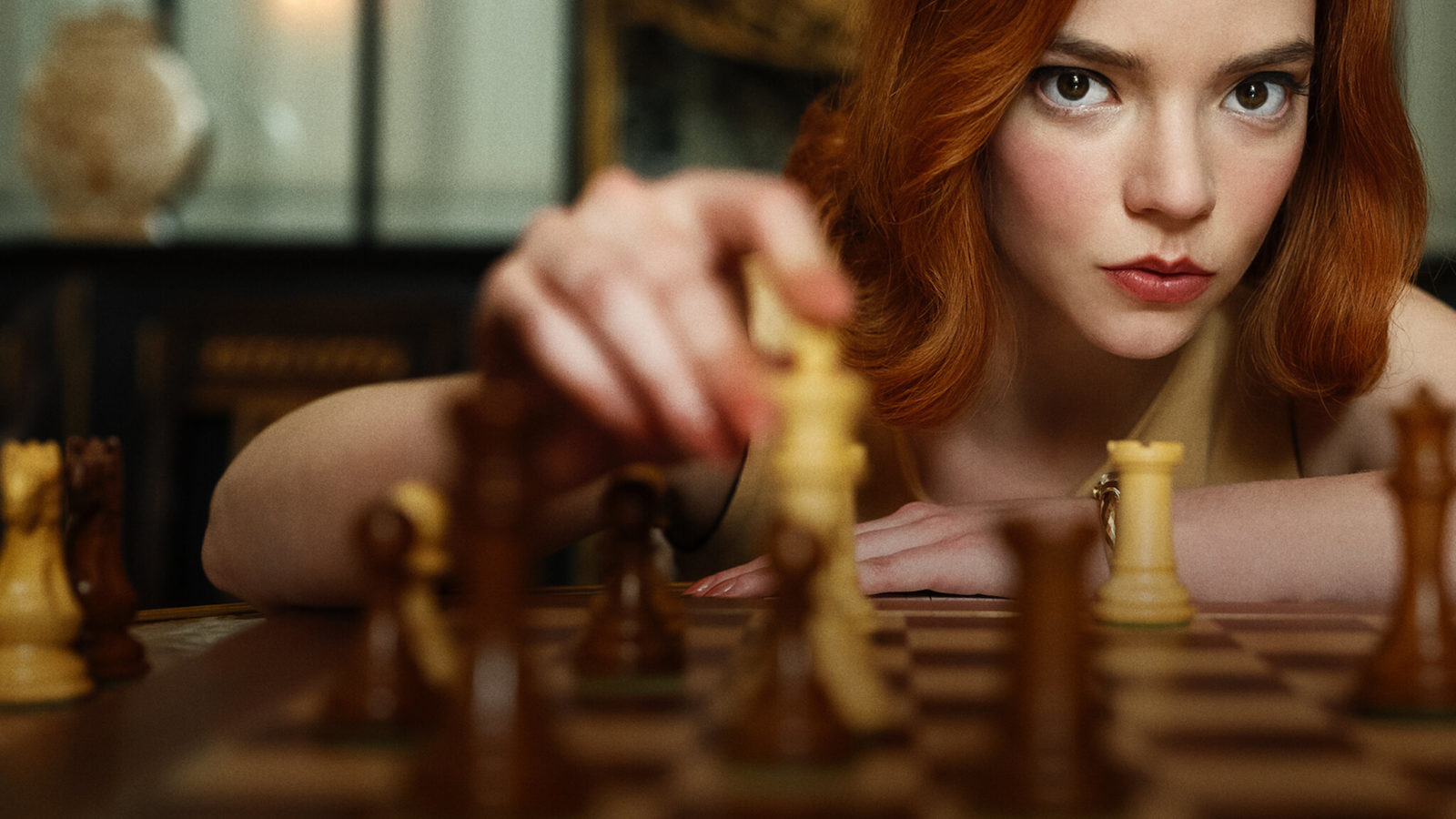 Beth Harmon looking over chess board into camera, finger on the king; Credit: Lifestyle Asia