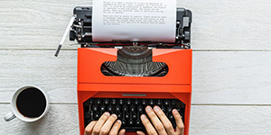 Orange typewriter being used