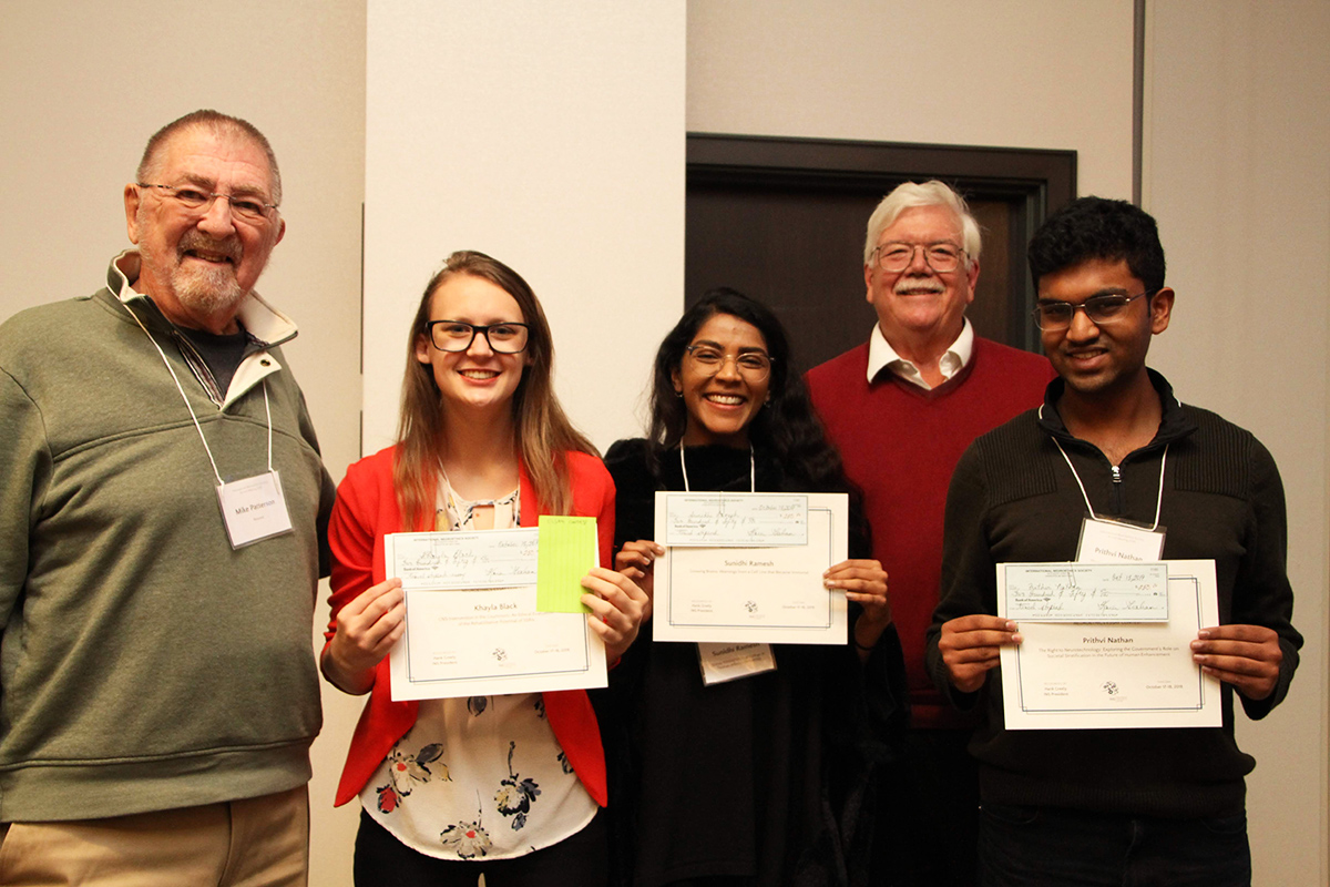 Photo of Michael Patterson presenting essay contest winners Khayla Black, Sunidhi Ramesh and Prithvi Nathan, with Hank Greely standing behind the winners