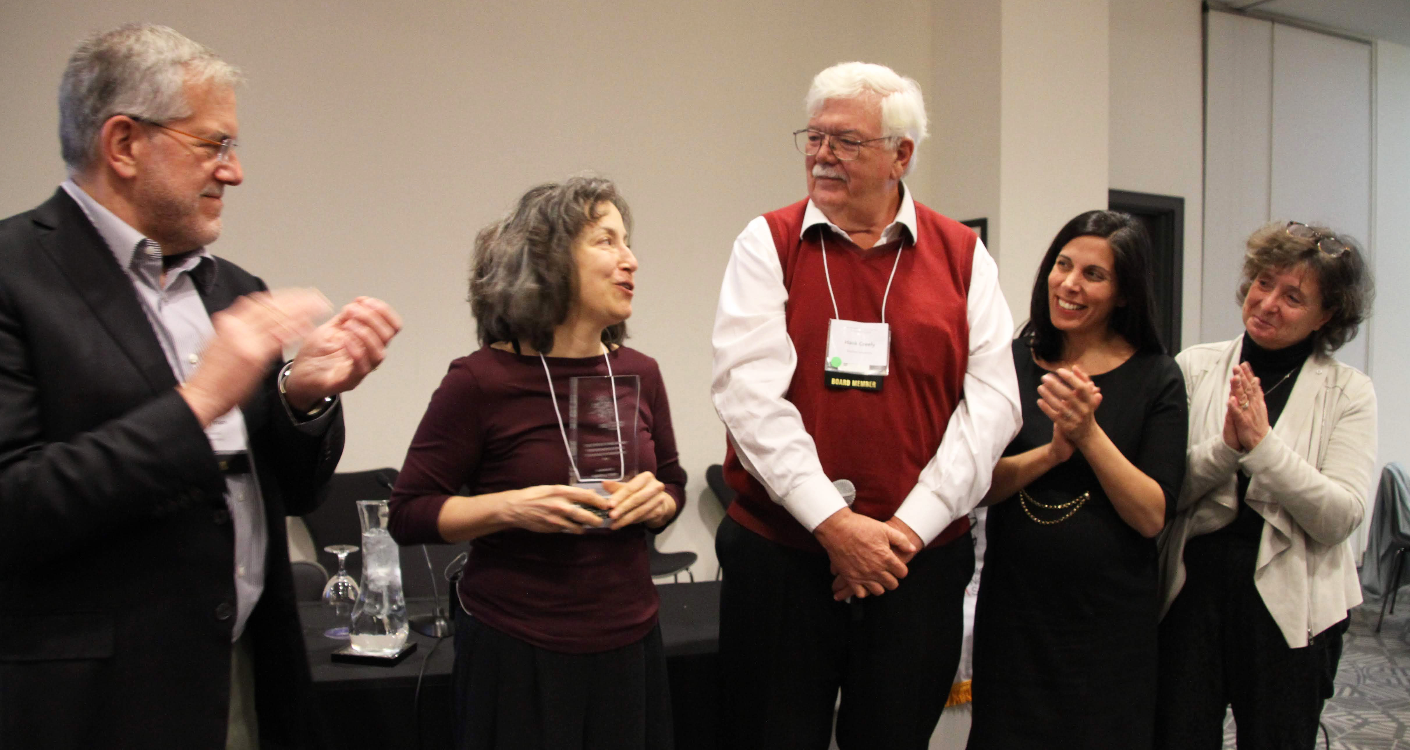 Photo of Steve Hyman, Martha Farah accepting an award plaque, Hank Greely, Nita Farahany and Judy Illes
